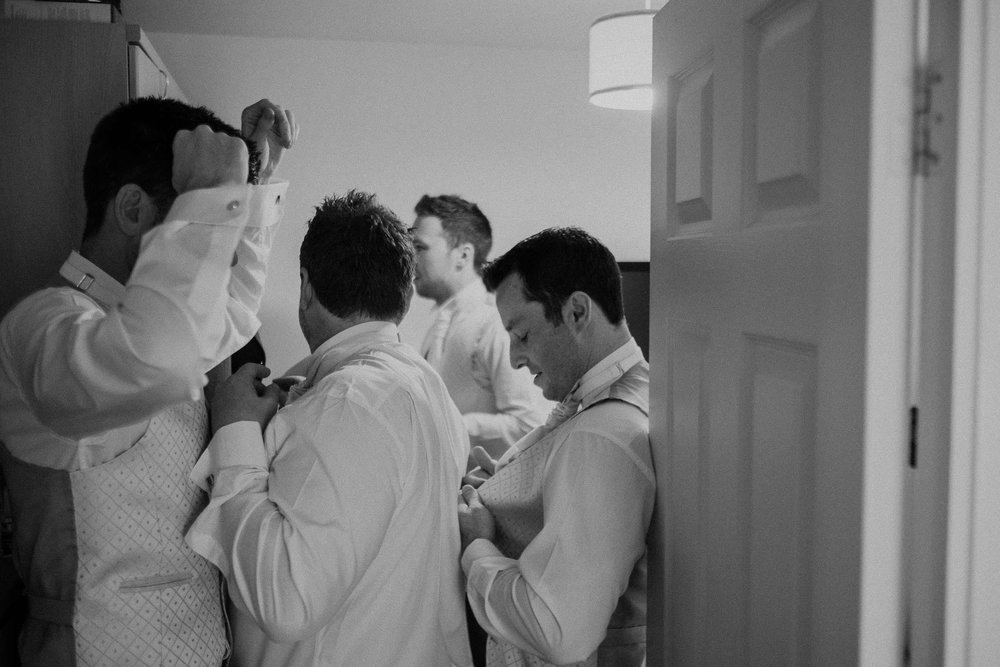 Black and white photo of groomsmen getting ready in tiny room