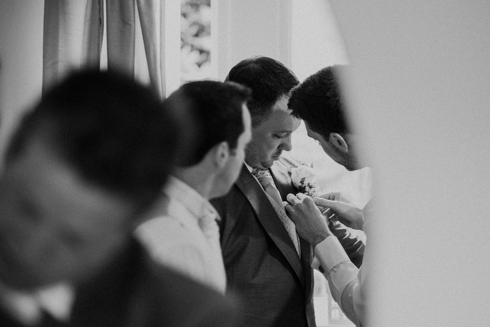 Black and white photo of groomsmen fixing groom's buttonhole flower