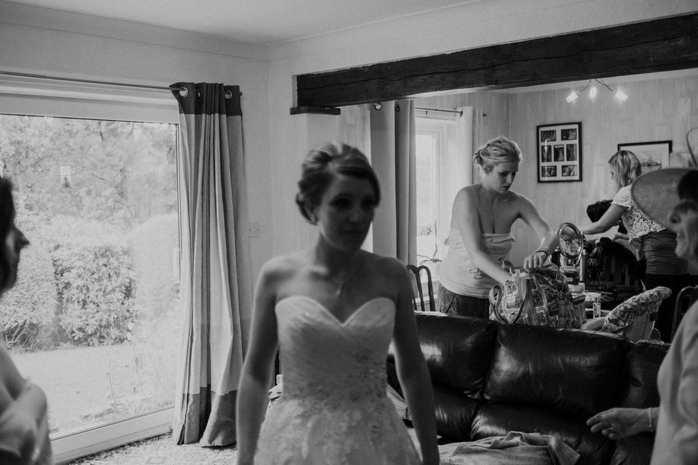Black and white photo of bridesmaids getting ready with bride out of focus in foreground
