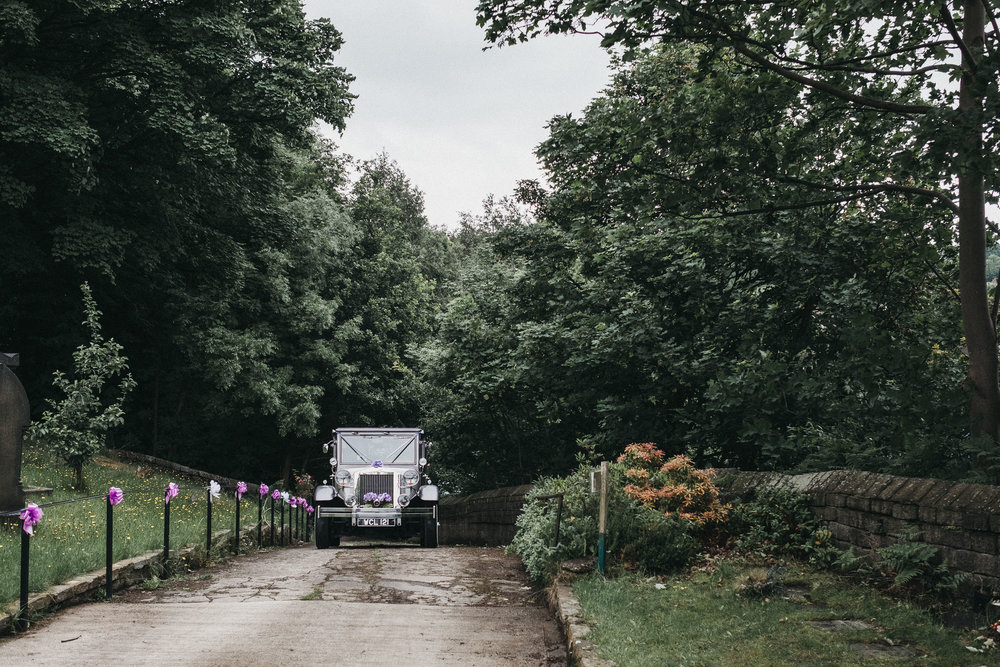Wedding car drives up narrow lane to church