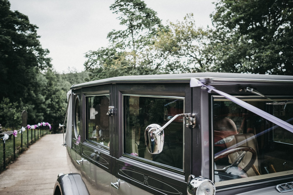 Wedding car arrives at church, silhouette of bride in back