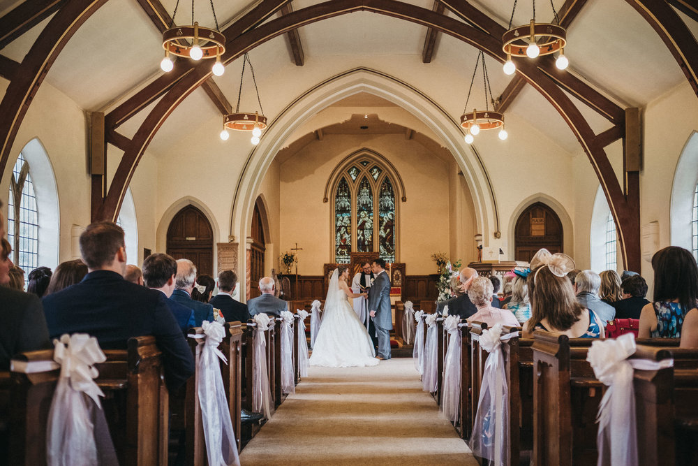 Wide photo of church showing guests watching wedding ceremony
