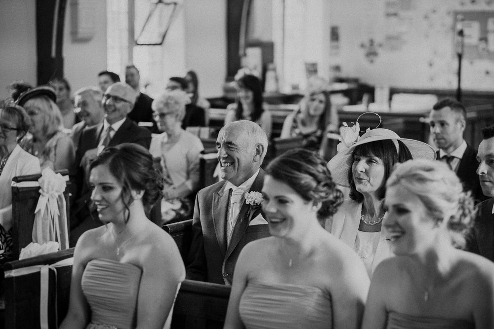 Black and white photo of guests laughing during wedding ceremony