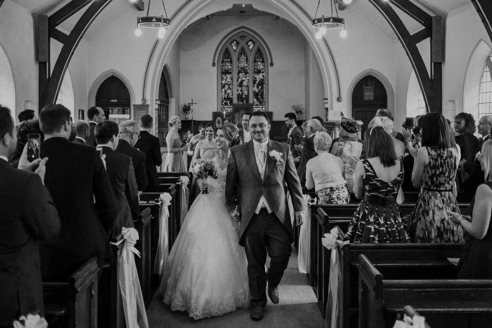 Black and white photo of bride and groom smiling as they leave the church