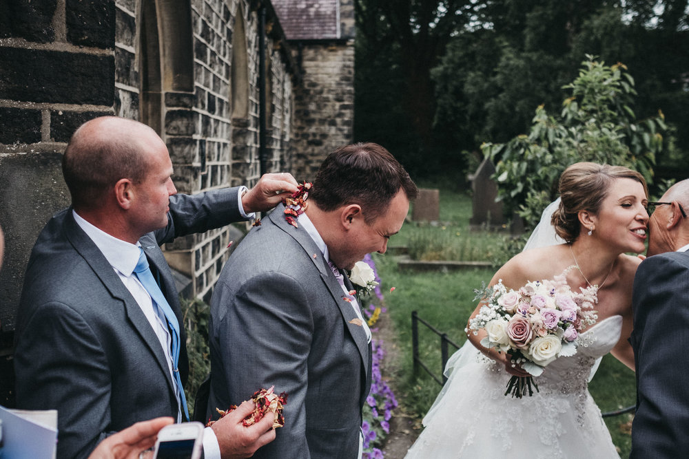 Funny photo showing wedding guest stuffing confetti down groom's neck