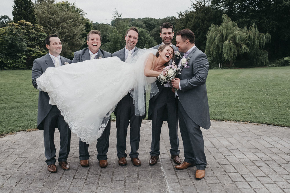 Groomsmen laugh as they hold up bride