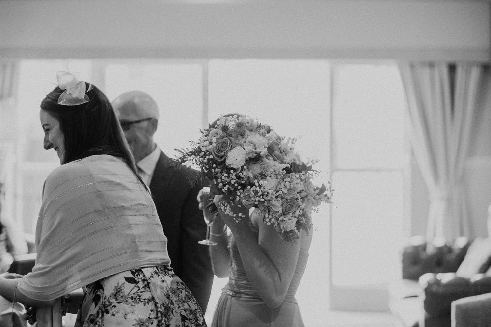 Black and white photo of bridesmaid holding flowers in front of her face