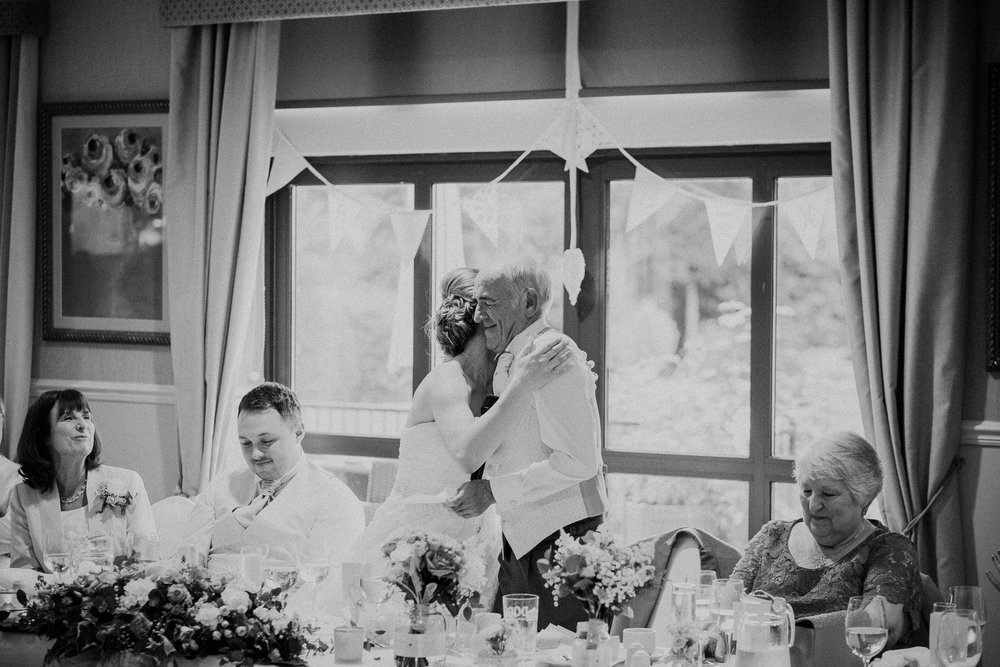 Black and white photo of bride hugging father during speeches