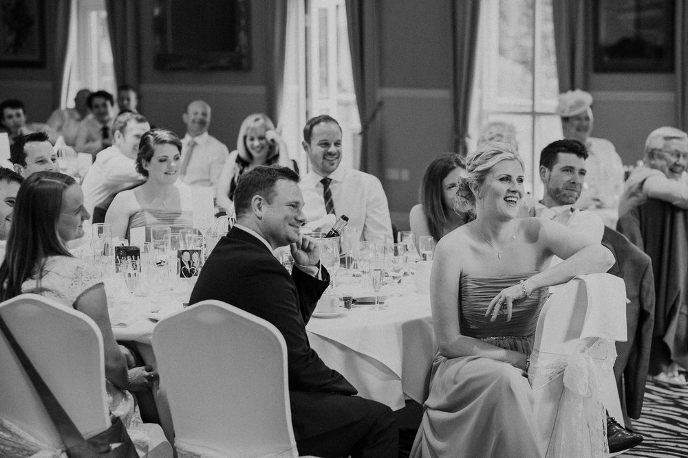 Black and white photo of guests watching wedding speeches