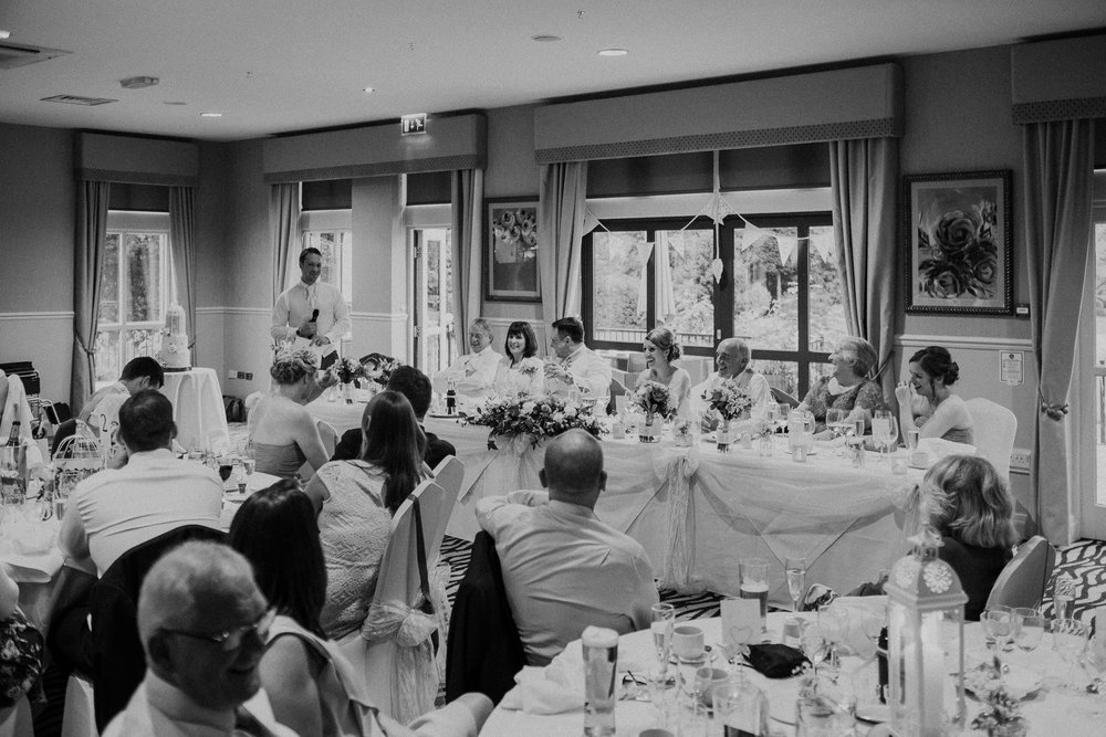 Black and white photo of best man's speech with guests watching