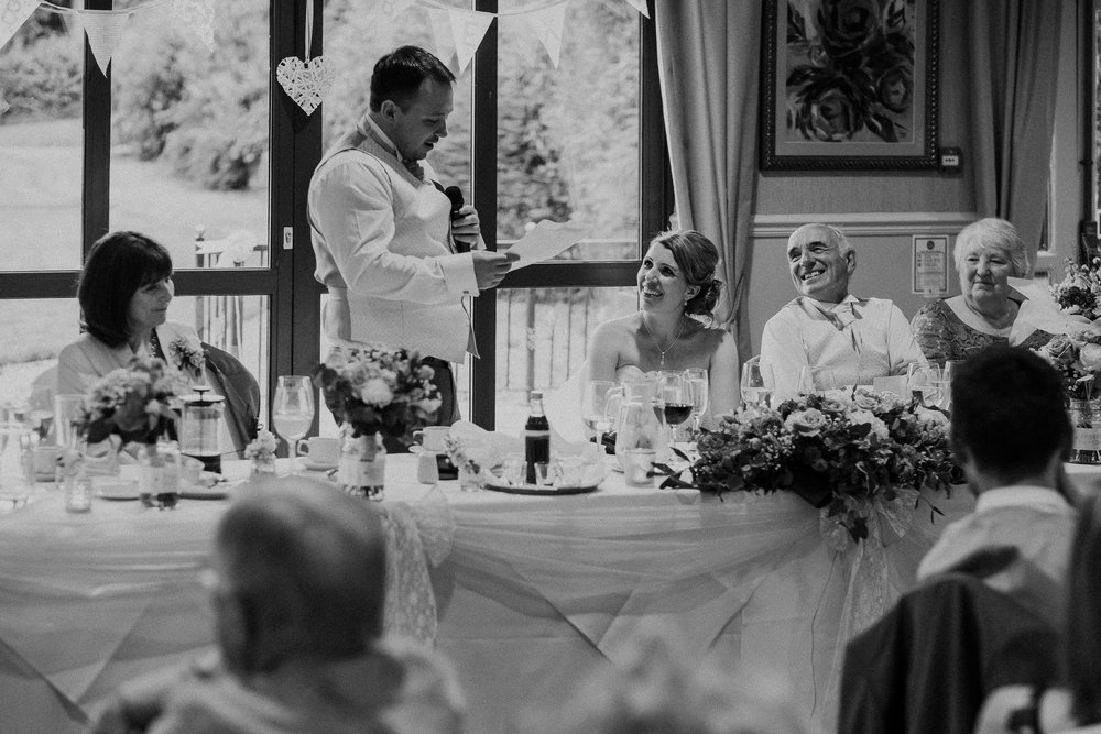 Black and white photo of bride and father of the bride laughing at Groom's speech