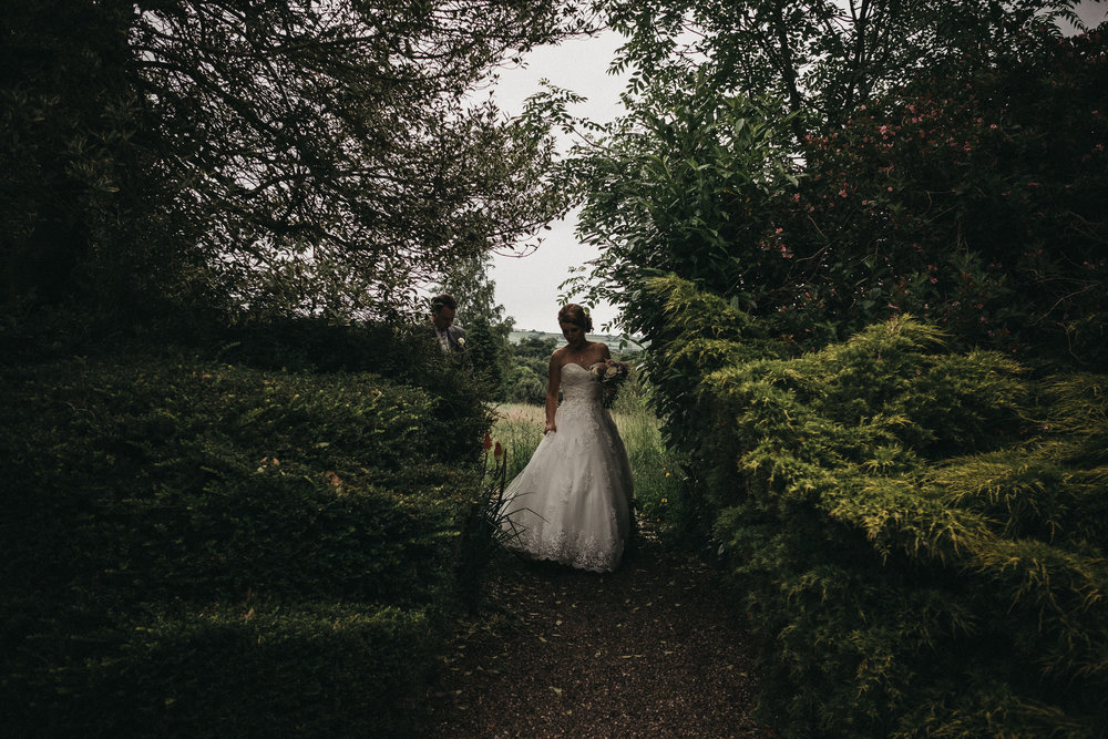 Moody photo of bride walking down narrow path between tall hedges