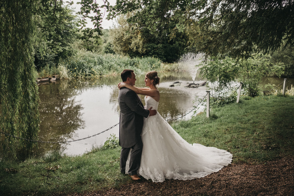 Bride and groom looking into each other's eyes while standing in front of pond
