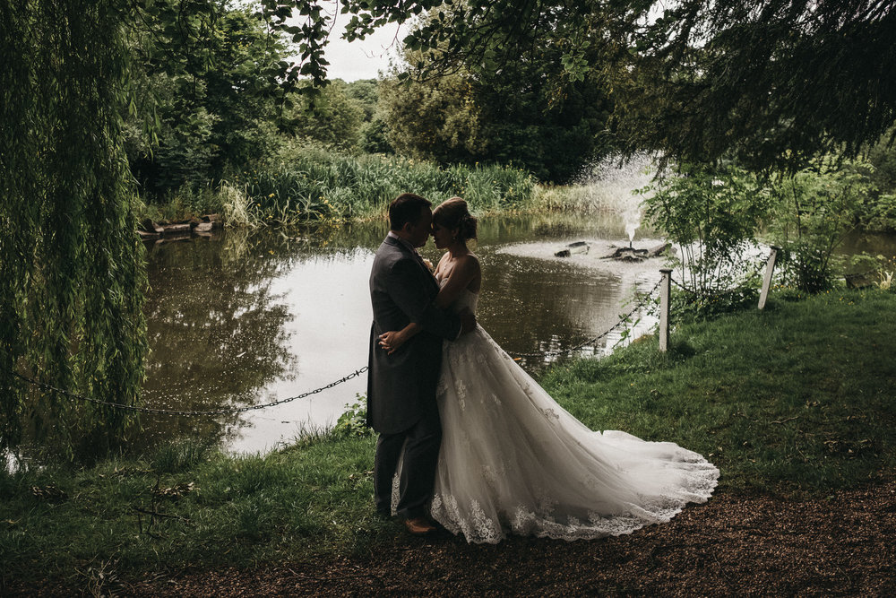 Moody photo of bride and groom cuddling in grounds of Bagden Hall
