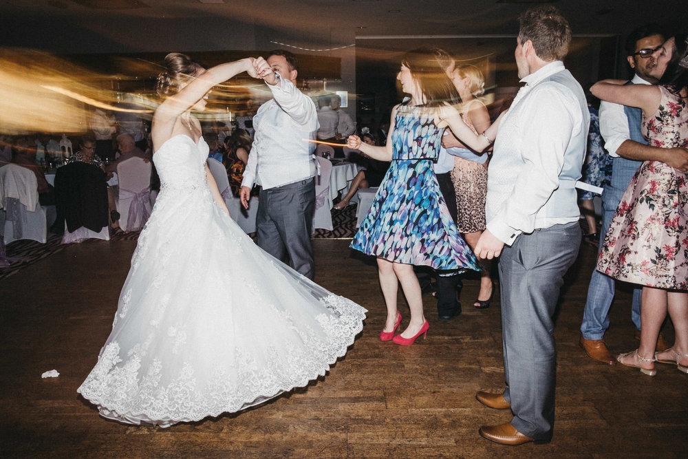 Groom twirls bride around on dance floor