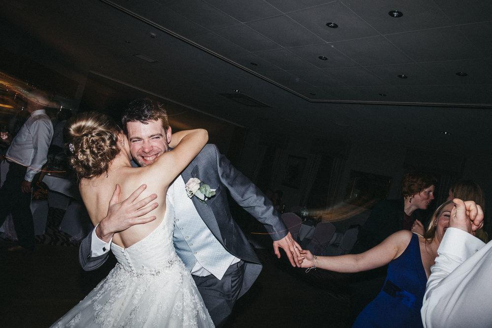 Groomsman hugs bride on dance floor