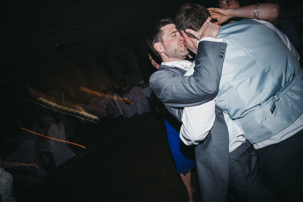 Groomsman kisses groom on dance floor