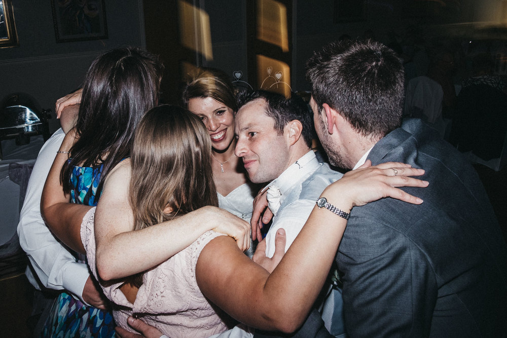 Bride and guests group hug on dance floor