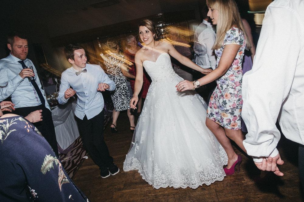 Guests dance around bride on wedding evening