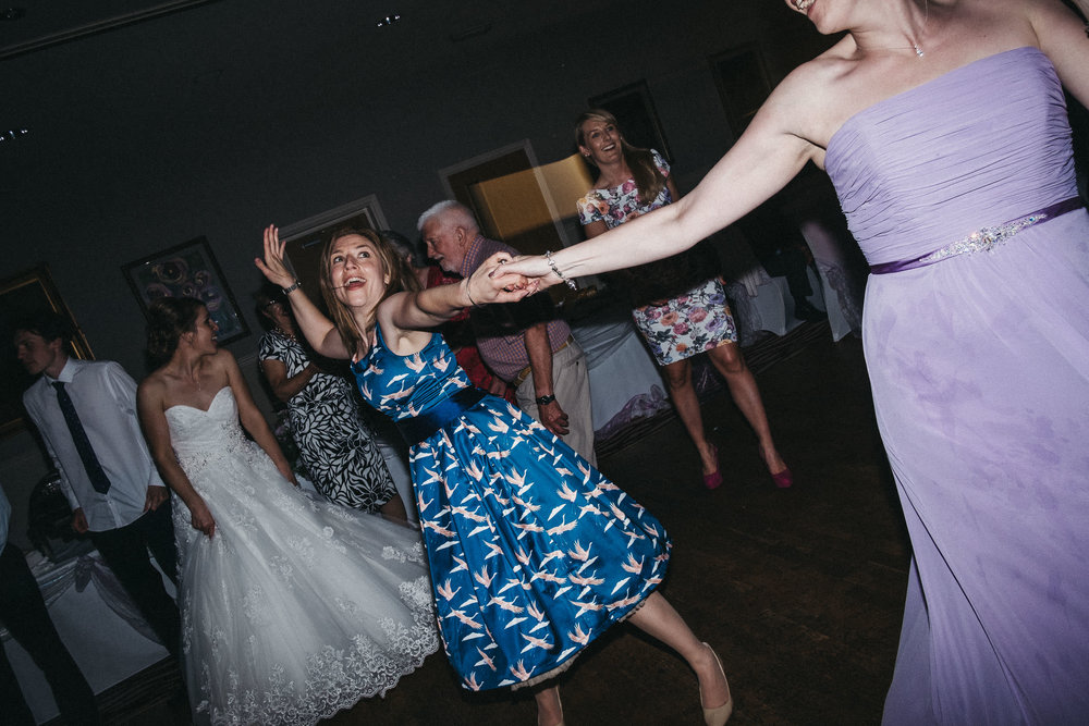 Bridesmaids hold hands and dance extravagantly
