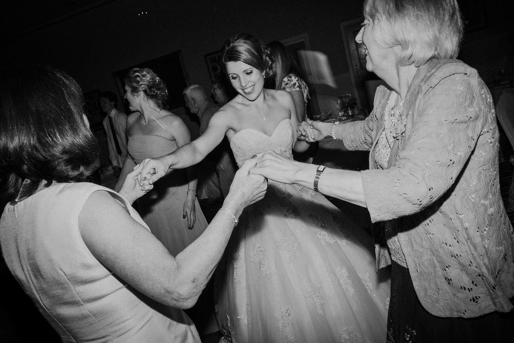 Black and white photo of bride dancing with older relatives