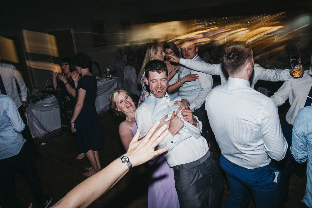 Bridesmaid grabs groomsman on dance floor