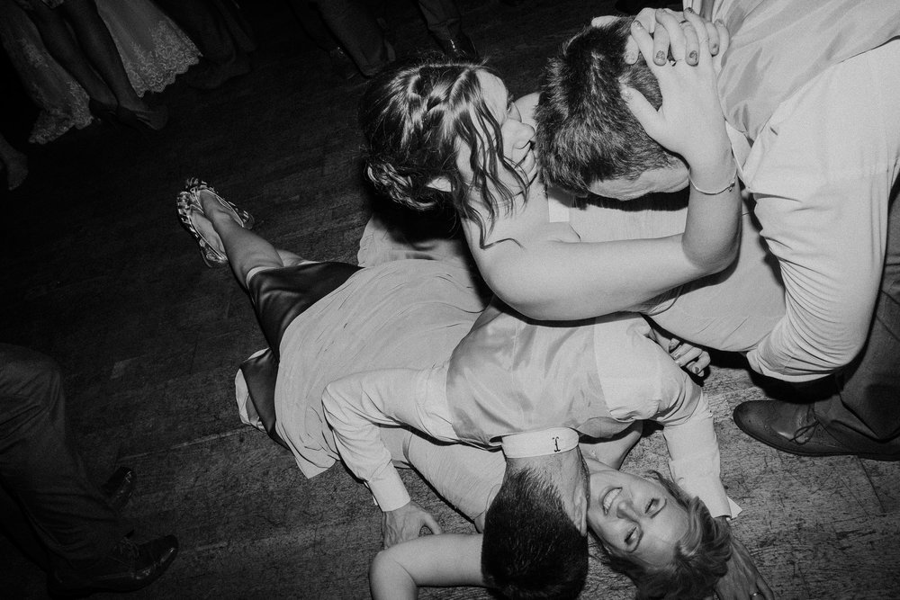 Black and white photo of bridesmaid and groomsman falling over another bridesmaid and groomsman on the floor