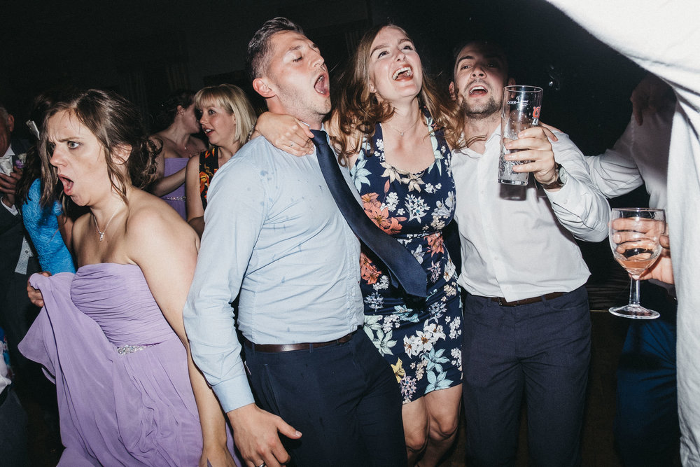 Wedding guests sing along to song on wedding dance floor