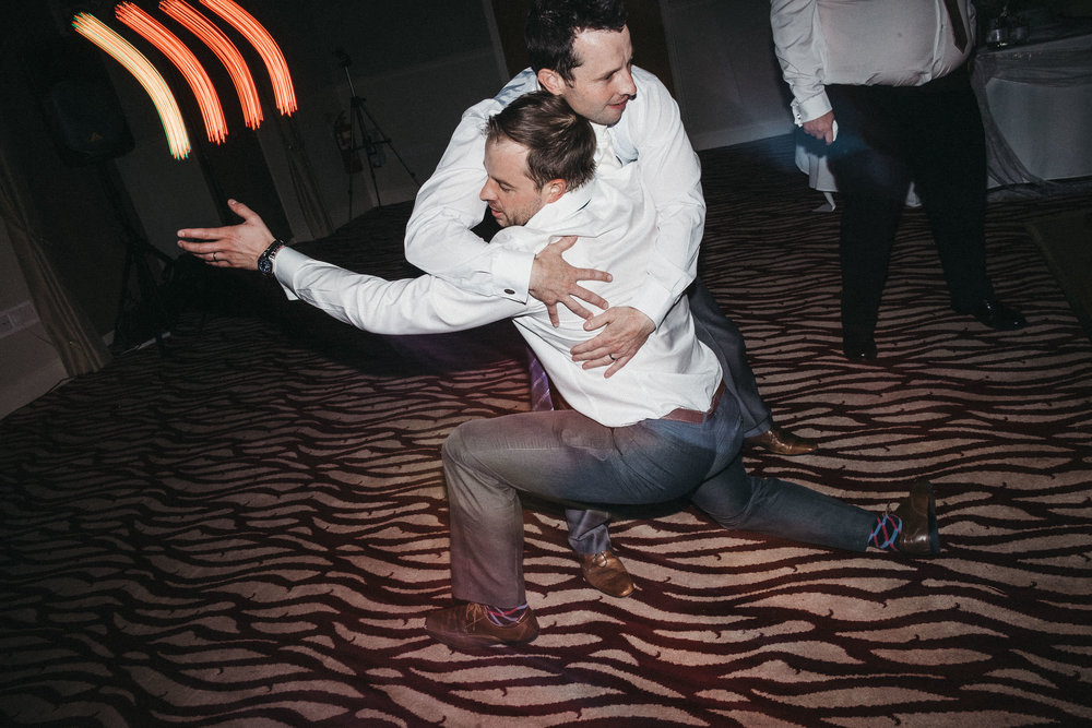 Groomsmen hold each other up while dancing crazily