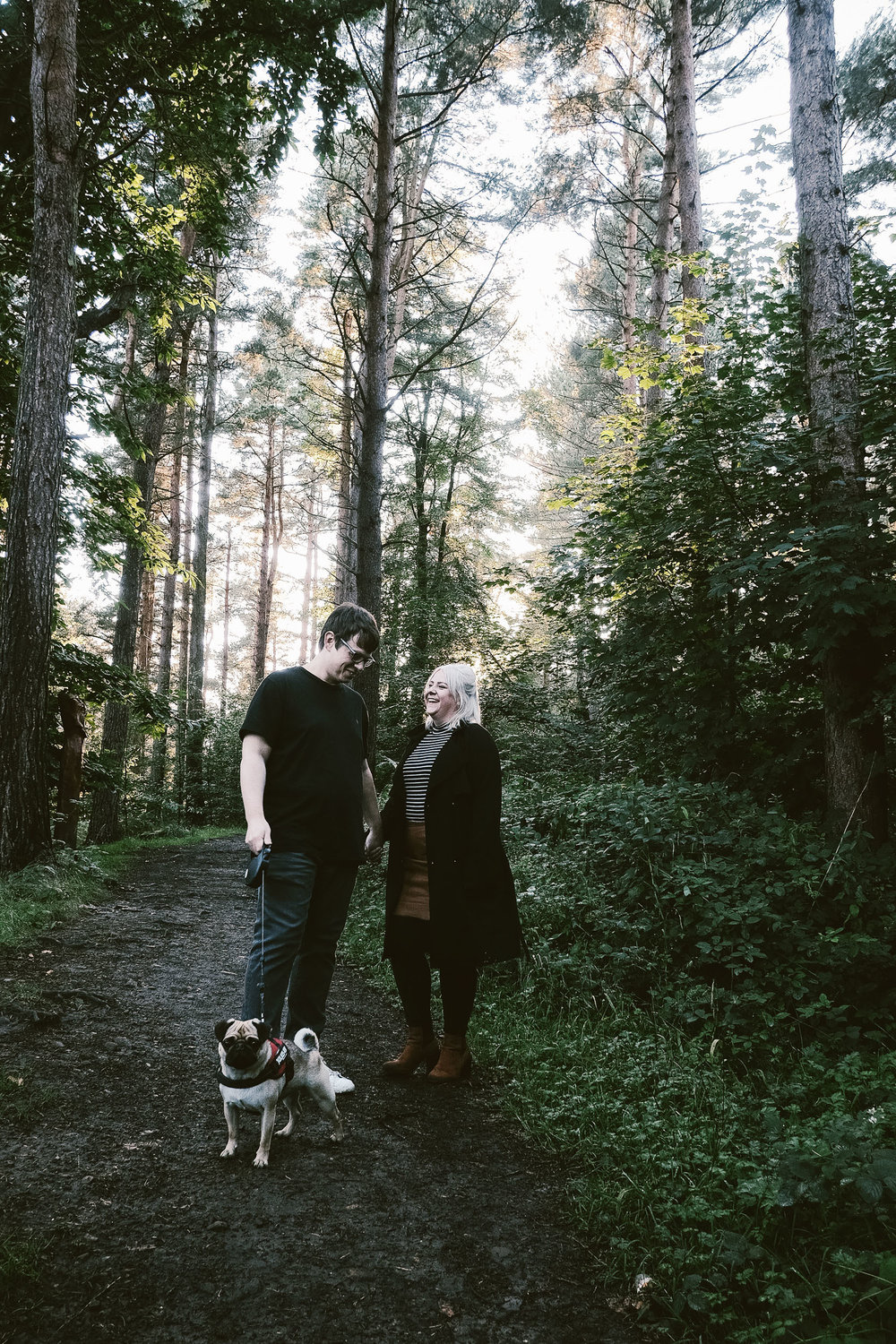 Couple with dog laughing in forest with sun breaking through trees