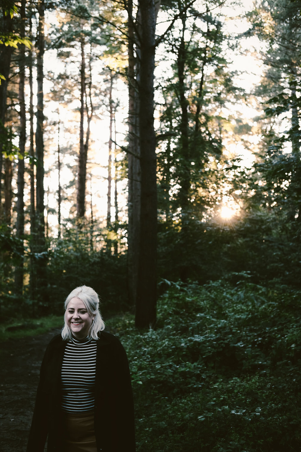 engaged woman laughs with dark forest and light breaking through trees behind