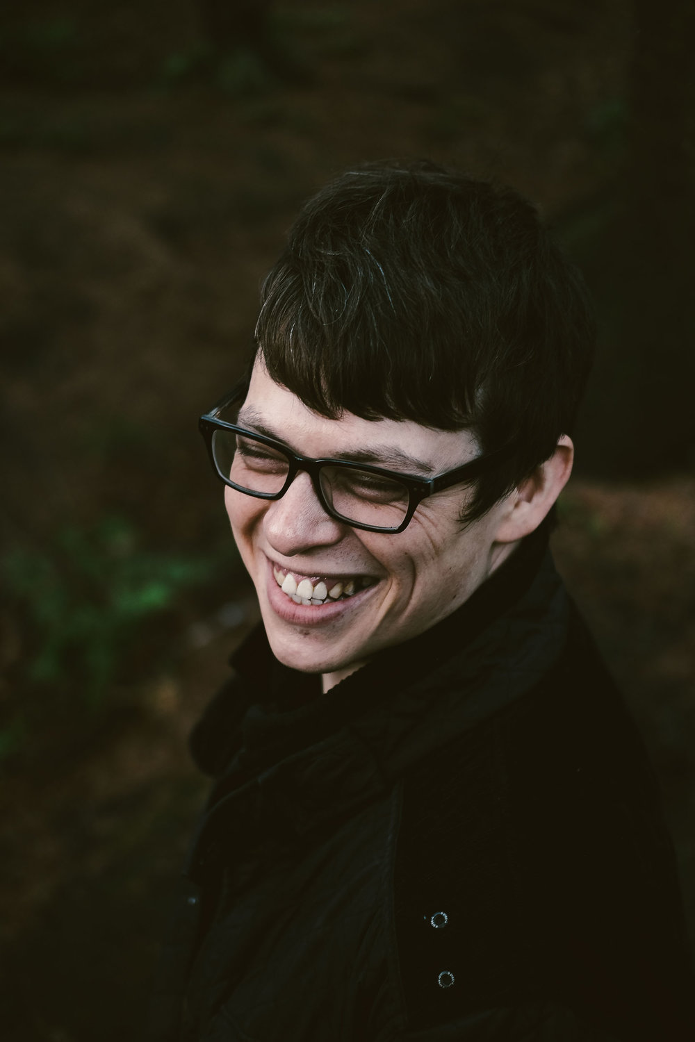 Man with glasses laughs in close up portrait