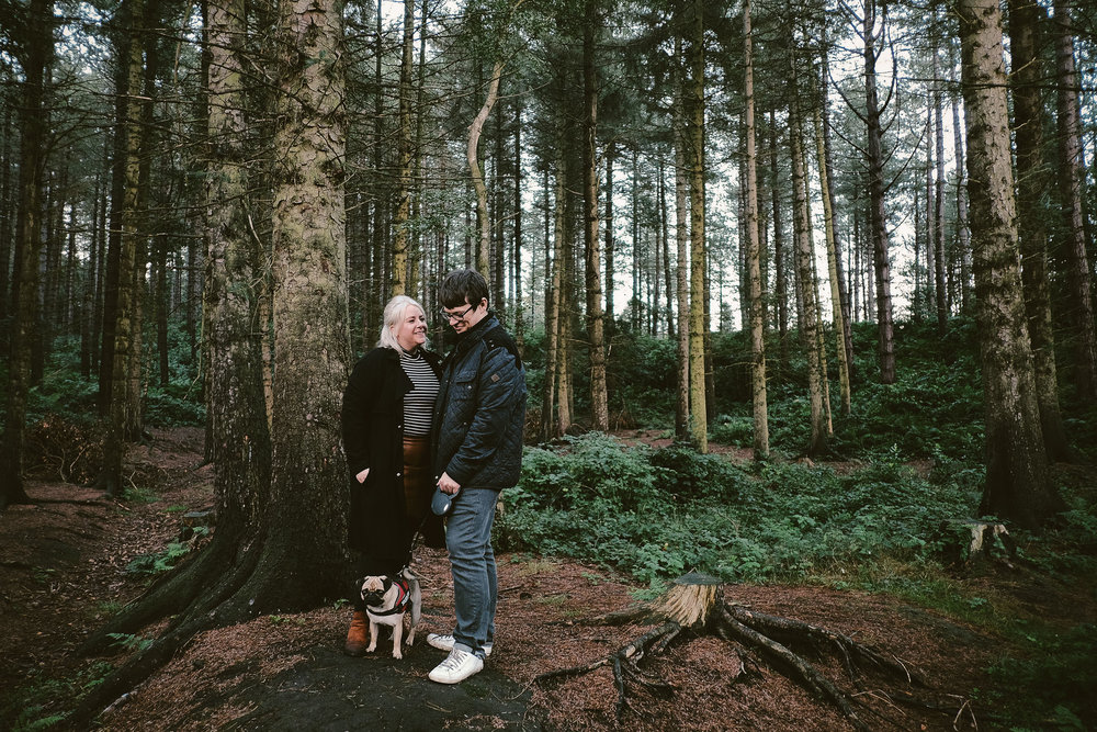 Couple cuddle while posing with dog in forest