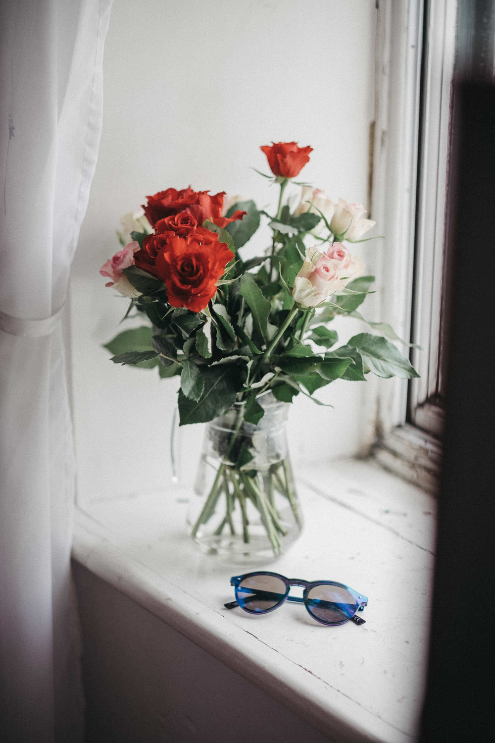 Roses on windowsill with sunglasses nearby