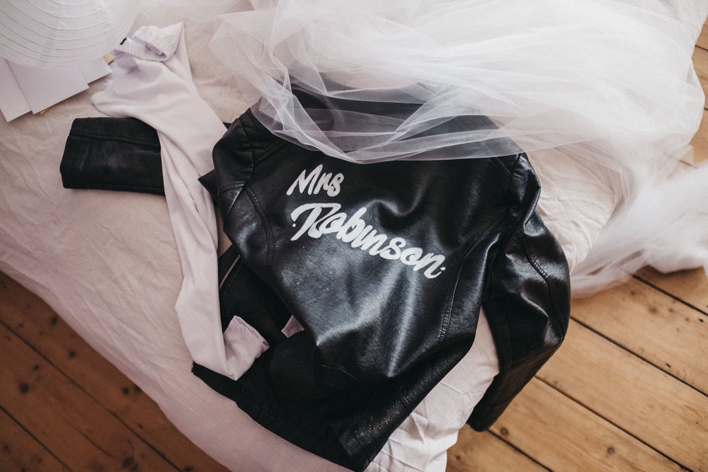 Bride's leather jacket lying on bed