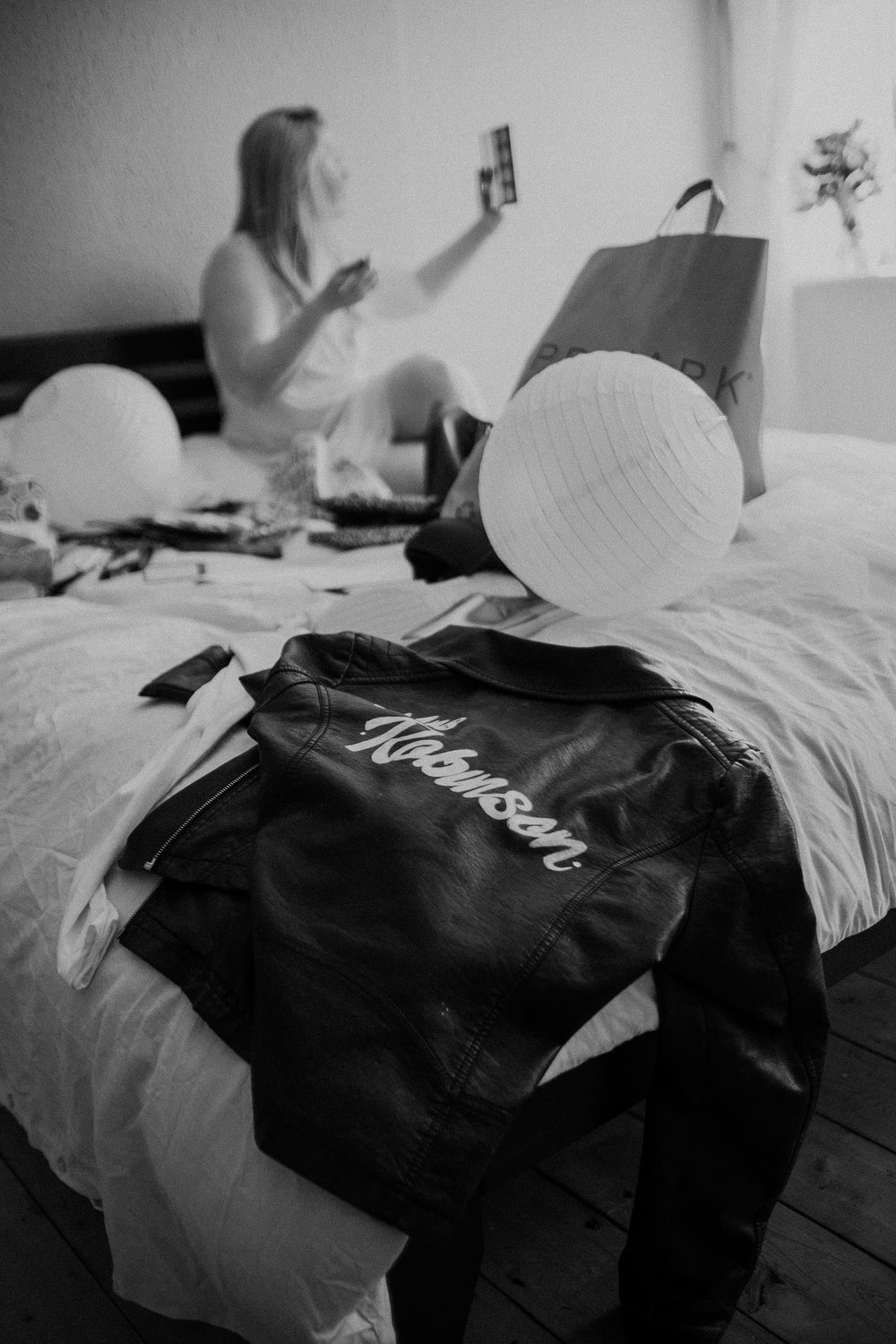 Black and white photo of bride's leather jacket with bride getting ready behind