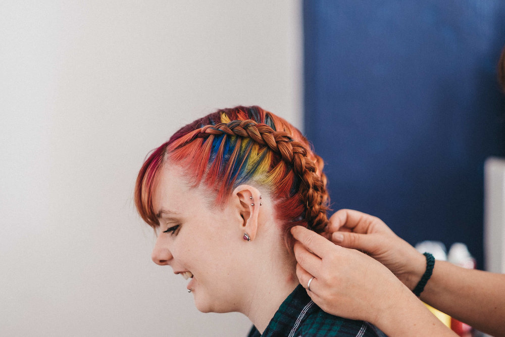 Bridesmaid getting hair styled in rainbow colours