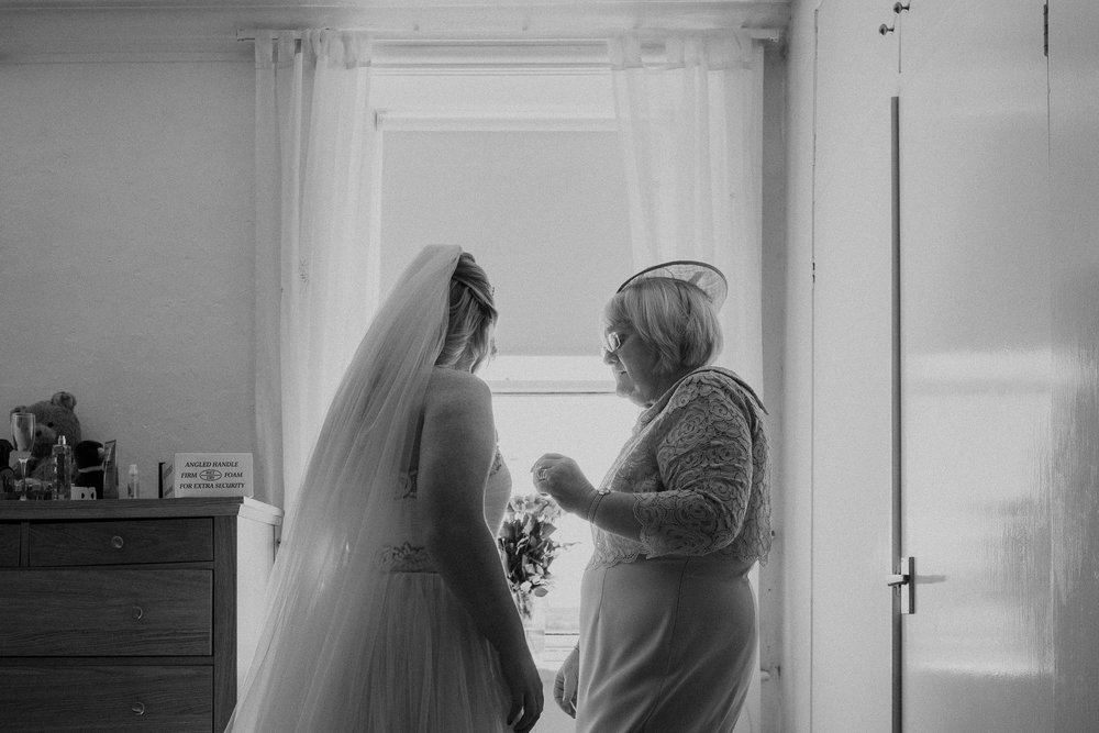Black and white photo of mother of the bride helping bride get ready