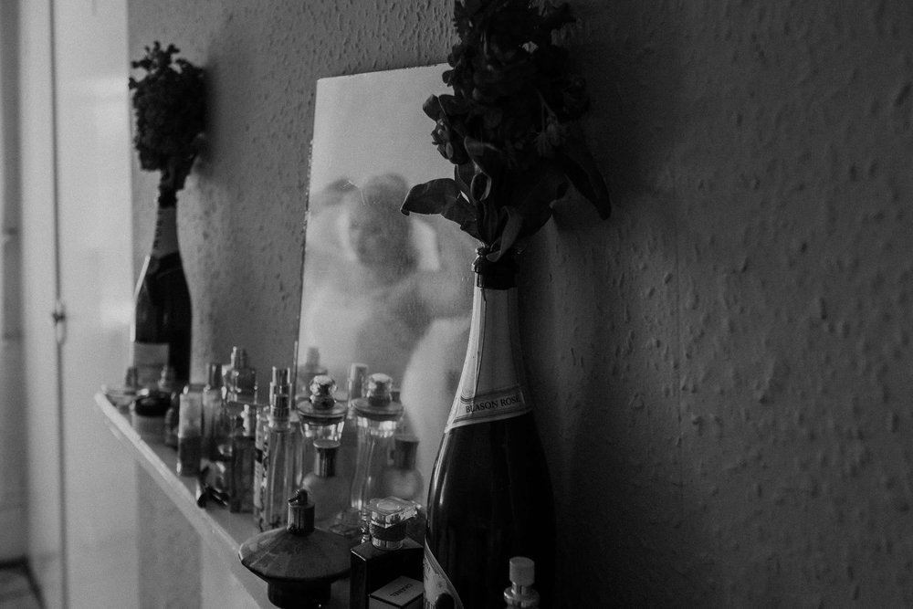 Black and white photo of champagne bottles filled with roses with reflection of bride in mirror