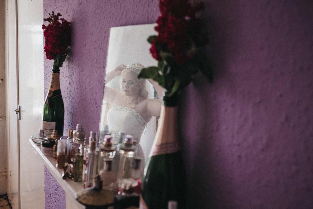 Reflection of bride in mirror adjusting veil
