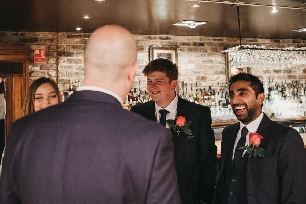 Groom laughing with wedding guests before ceremony