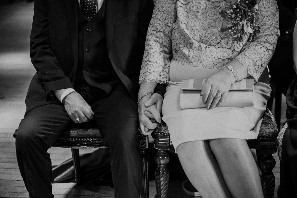 Black and white photo of mother and father of the bride holding hands