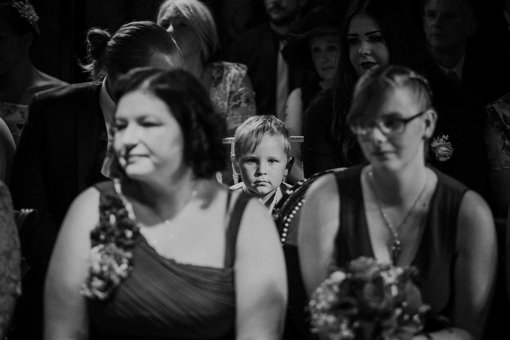 Black and white photo of child looking at camera during wedding ceremony