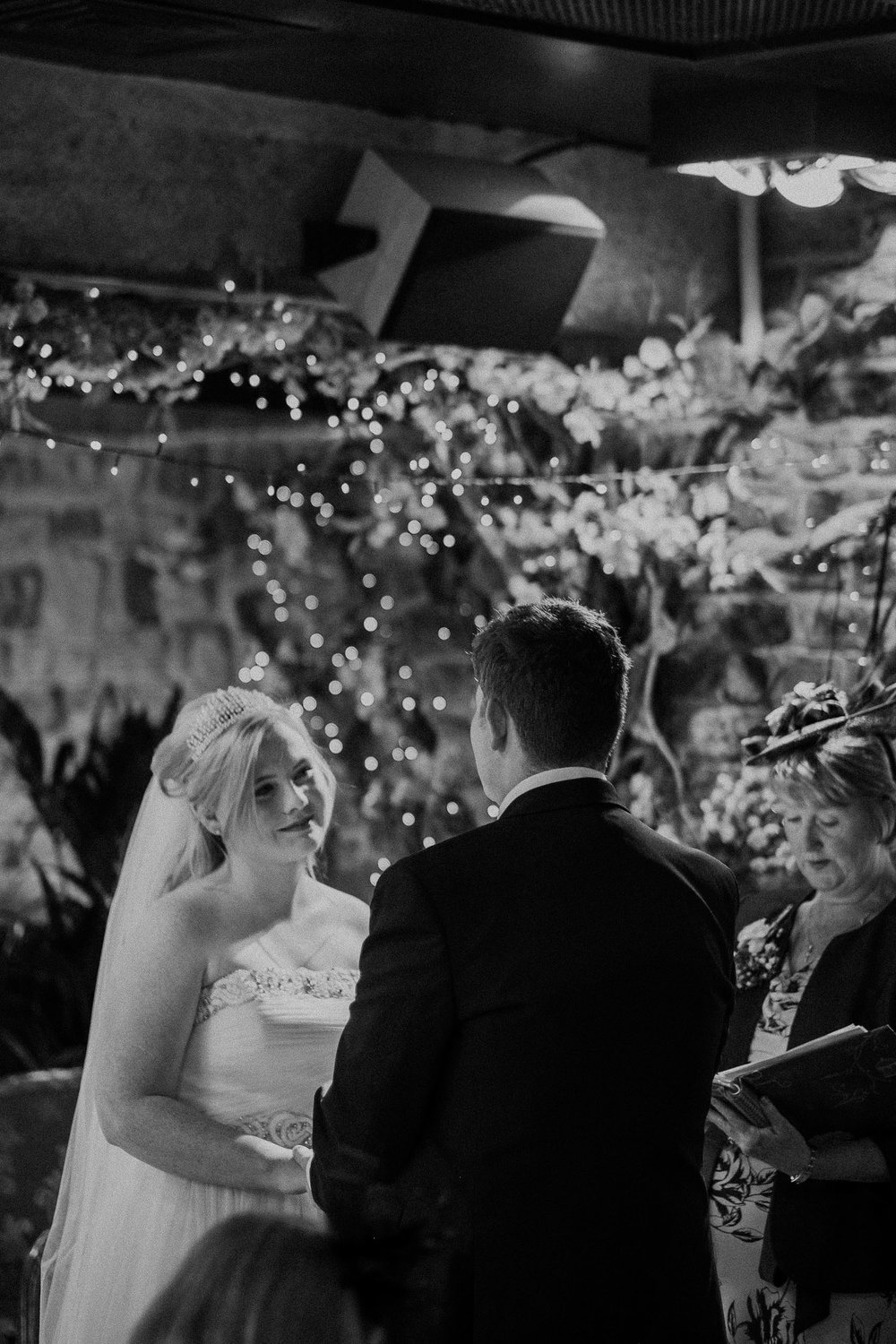 Black and white photo of bride looking longingly at groom during ceremony