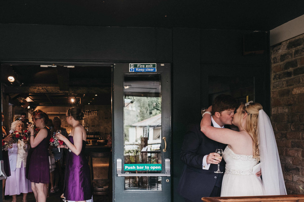 Bride and groom kiss while guests mingle through doorway