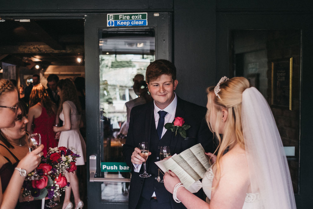 Bride reads wedding certificate while groom looks on
