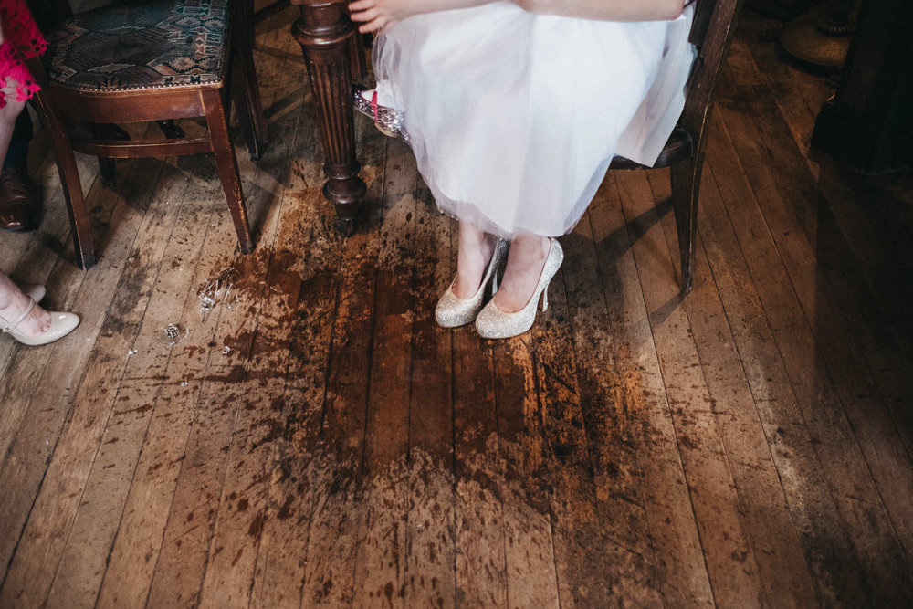 Guest sits with glitter covered shoes in spilt drink