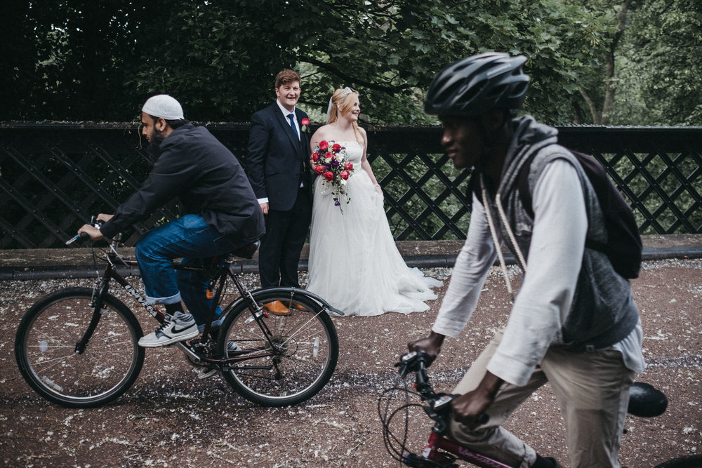 Bride and groom laughing as cyclists ride past
