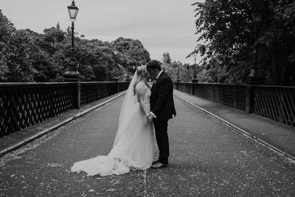 Black and white photo of bride and groom kissing on bridge