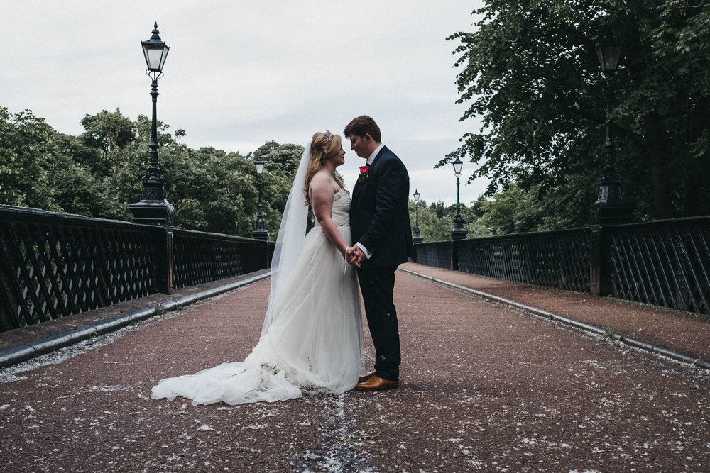 Bride and groom hold hands and look into each others eyes while standing on bridge